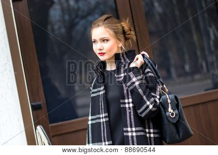 Young Beautiful Girl With A Fashionable Bag Is Standing On The Street