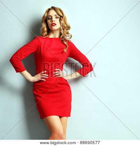 Beautiful young woman in red dress posing on light blue background