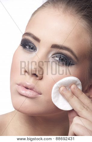 Young woman removing make-up