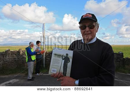 Cedric Robinson with his book at Morecambe Bay