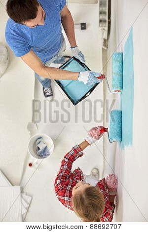 repair, building, people, teamwork and renovation concept - couple with paint and rollers painting wall at home
