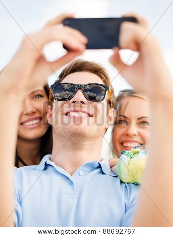 summer holidays, vacation, happy people concept - group of friends taking selfie with cell phone on the beach
