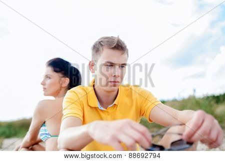 friendship, summer holidays, relations, break up and people concept - unhappy couple sitting on beach