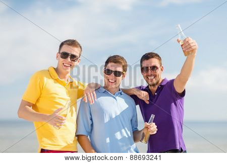 summer holidays, vacation, people and bachelor party concept - group of happy male friends having fun and drinking beer on beach