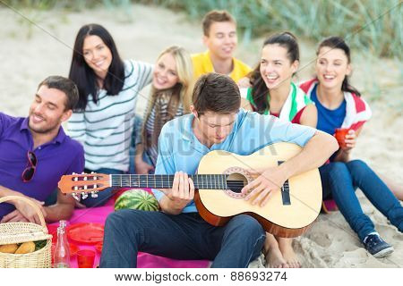 summer holidays, vacation, music, happy people concept - group of happy friends playing guitar on beach