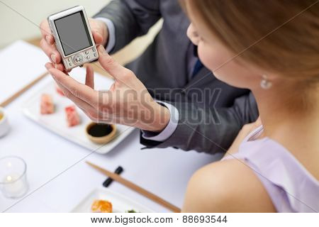 people, leisure, eating, food and technology concept - close up of couple with camera and sushi at restaurant