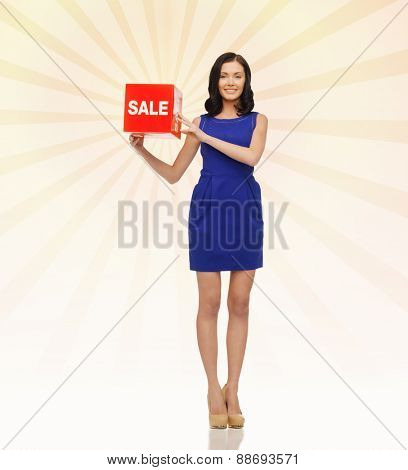 people, business, retail, shopping and consumerism concept - happy young woman in dress with red sale sign over beige burst rays background