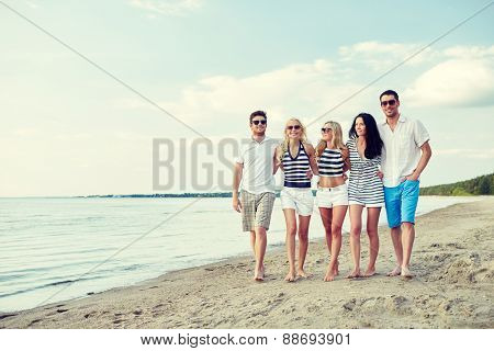 summer, holidays, sea, tourism and people concept - group of smiling friends in sunglasses walking on beach
