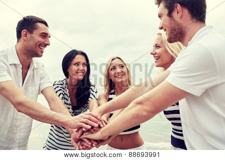 friendship, happiness, unity and people concept - smiling friends putting hands on top of each other