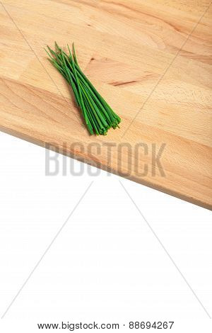 Green chives on wooden chopping board