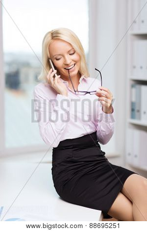 education, business, technology, communication and people concept - smiling businesswoman or secretary wearing eyeglasses calling on smartphone  in office