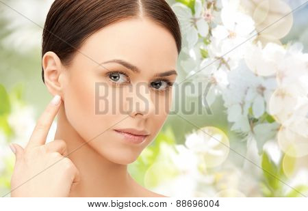 people, beauty, hearing and healthcare concept - face of beautiful woman touching her ear over green blooming garden background