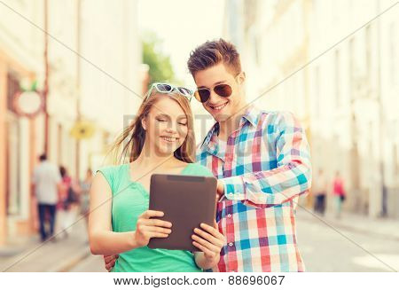 travel, vacation, technology and friendship concept - smiling couple with tablet pc computer in city