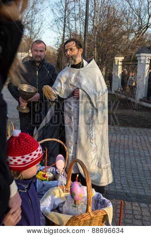 Moscow - April 11, 2015: Orthodox Priest Sprinkles Easter Eggs And Cakes Holy Water