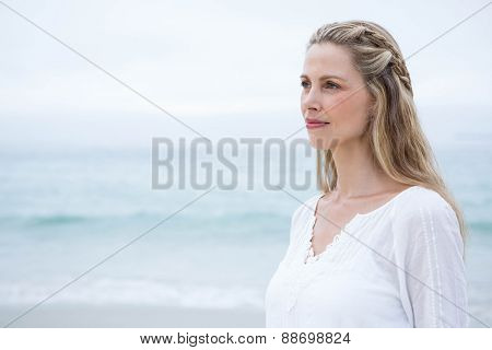 Smiling blonde standing by the sea at the beach