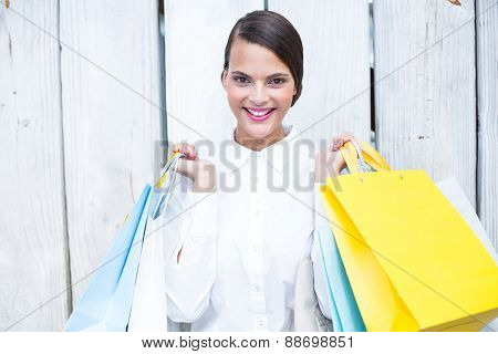 Beautiful brunette holding shopping bags in front of wooden grey planks