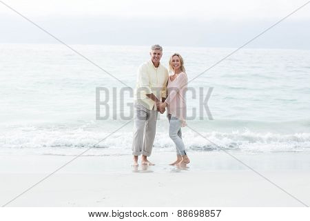 Happy couple standing by the sea at the beach