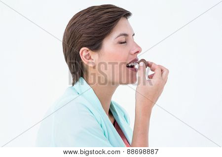 Pretty brunette eating chocolate candy on white background