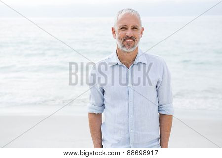 Smiling man standing by the sea hands in pocket at the beach