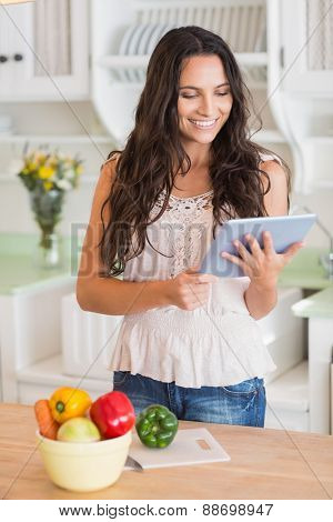 Pretty brunette using tablet pc and preparing salad in the kitchen