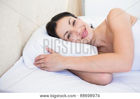 Pretty brunette smiling on bed at home