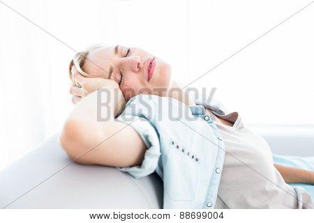 Blonde woman having headache in the living room