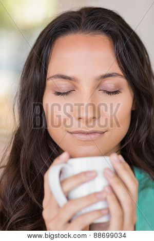 Pretty brunette smelling her coffee at home in the living room