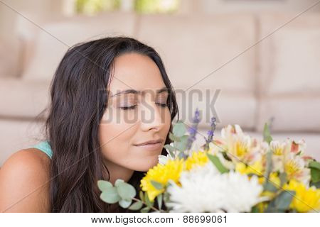 Pretty brunette lying on the floor and smelling the flowers at home in the living room