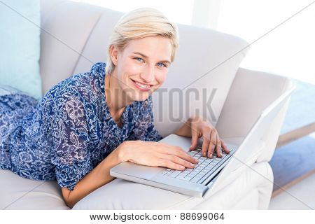 Pretty blonde woman lying on the couch and using her laptop in the living room