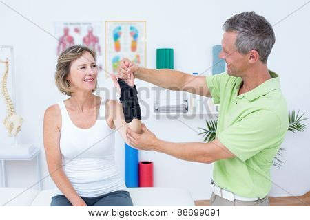 Doctor examining his patients wrist in medical office