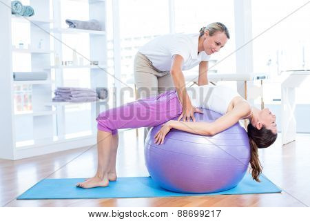 Trainer helping woman on exercise ball in medical office