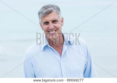 Smiling man looking at camera at the beach