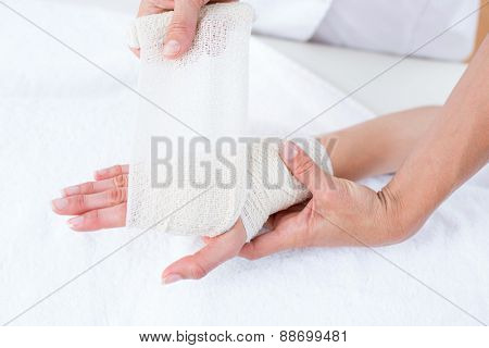 Doctor bandaging her patient wrist in medical office