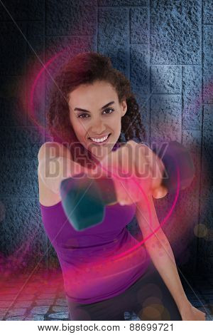 Fit woman lifting blue dumbbell against dark grey room