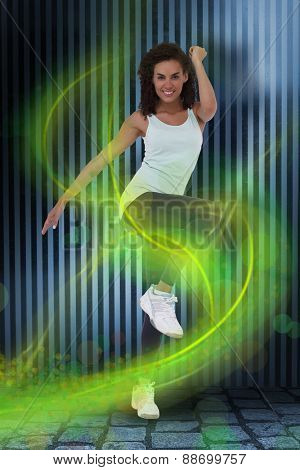 Fit woman doing aerobic exercise against dark grey room