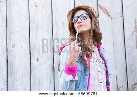 Pretty brunette posing and holding paint brush against wooden planks