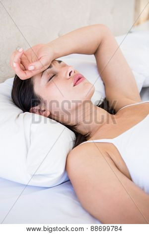 Pretty brunette with migraine on bed at home