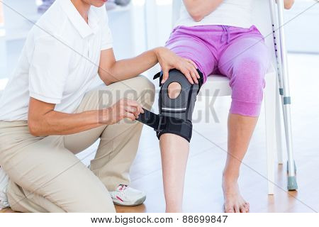 Doctor examining her patients knee in medical office