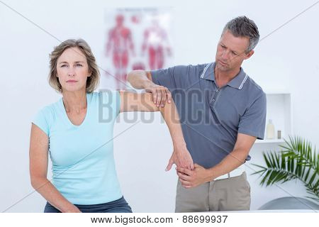 Woman stretching her arm with her doctor in medical office