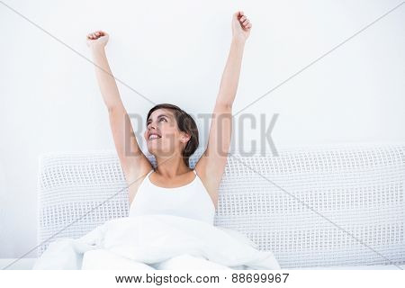 Happy woman waking up at home in the bedroom
