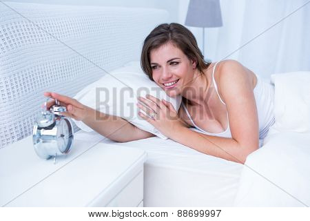 Happy brunette extending hand to alarm to clock in bed at home in the bedroom