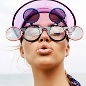 image of tropical island  - Young pretty hot sexy woman on the tropic island in summer near the sea and blue sky giving air kiss and having fun in yellow sunglasses - JPG