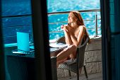 stock photo of nearly nude  - Young and pretty woman enjoying morning on the balcony near the sea - JPG