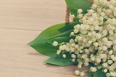 stock photo of lilly  - fresh lilly of the valley flowers posy on wooden background retro toned - JPG