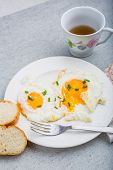 image of chives  - Two fried eggs with chives on white plate - JPG
