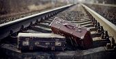 picture of old suitcase  - Two old vintage suitcases thrown on railway rails - JPG