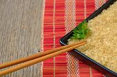 picture of chinese parsley  - Plate with brown uncooked rice and leaf of parsley - JPG