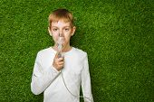 picture of inhalant  - Portrait of a boy breathing through inhaler mask over spring green grass background - JPG