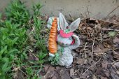 stock photo of figurines  - Spring Bunny Figurine Stands Guard in the Garden - JPG