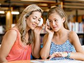 pic of mums  - A teenage girl with headphones sitting in a library with her mum - JPG